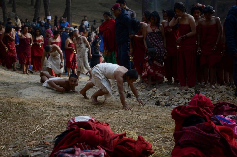 Nepalese Hindu devotees prostrate themselves after taking part in a mass bathing ritual during the month-long Swasthani Festival in Changu Narayan at Bhaktapur, on the outskirts of Kathmandu on February 8, 2017. Hundreds of married and unmarried women in the Himalayan nation are marking the month-long fast in the hope of a prosperous life and conjugal happiness. (Prakash Mathema/AFP/Getty Images)