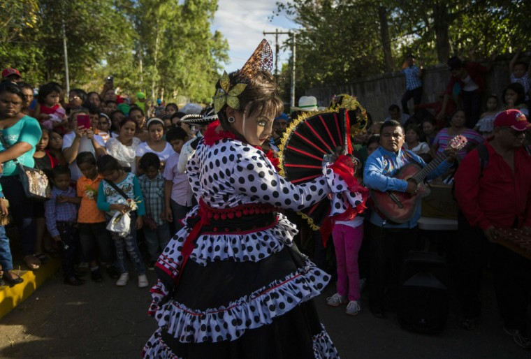 "A woman dressed as a traditional character in the ""Baile de Negras"" dances on the feast day of the Virgin of the Candelaria (Candlemas) in the town of Diriomo, some 45 km from Managua, Nicaragua on February 2, 2017. Candlemas falls forty days after Christmas and is celebrated by Catholics as the presentation of Christ at the Temple. (AFP Photo/Inti Ocon)"