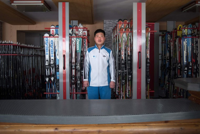 In this photo taken on February 20, 2017, Kim Chol-Nam, 30, poses for a portrait at the ski hire desk where he works at the Masikryong, or Masik Pass, ski resort near Wonsan. The resort was opened in 2013. A price list at the ticket desk advertises a cost of 80 US dollars for a one-day lift pass and ski hire for foreign tourists, while North Koreans can expect to pay the equivalent of around 40 US dollars. /  (AFP Photo/Ed Jones)