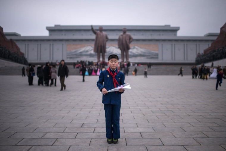 In this photo taken on February 16, 2017, Kim Su-Min, 11, poses for a portrait before offering flowers to the statues of late North Korean leaders Kim Il-Sung (top L) and Kim Jong-Il (top R) at Mansudae hill in Pyongyang. Kim Su-Min was observing the anniversary of the birth of late North Korean leader Kim Jong-il, a public holiday known as the 'Day of the Shining Star', during which residents of Pyongyang leave flowers at the feet of the statue. / (AFP Photo/Ed Jones)