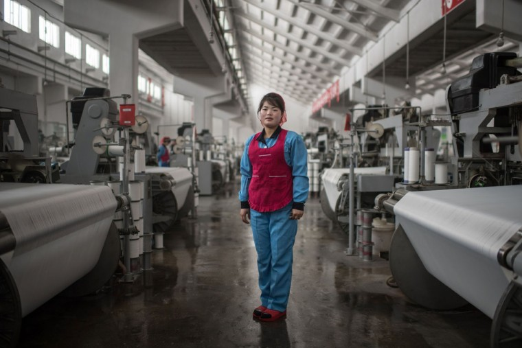 In this photo taken on February 22, 2017, Kim Jin-Hyang, 21, poses for a portrait at the Kim Jong-Suk textile mill in Pyongyang. A regular fixture on the itineraries of foreign journalists and tourists, the Kim Jong-Suk textile mill is named after the grandmother of current North Korean leader Kim Jong-Un. / (AFP Photo/Ed Jones)