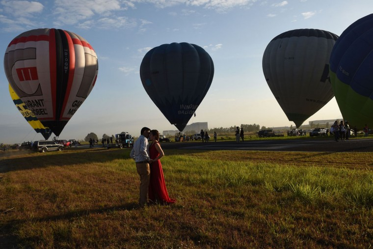 A couple poses for their pre-nuptial photo session in front of balloons taking flight during the annual International Hot Air Balloon Festival at the former Clark US Air Force base in Pampanga province, north of Manila on February 9, 2017. Some 29 balloon enthusiasts from around the globe are participating in the event which runs February 9 to 12. (TED ALJIBE/AFP/Getty Images)
