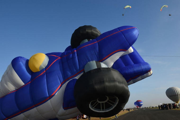 A balloon in the shape of a race car is inflated as powered paragliders (top R) are seen in flight during the annual International Hot Air Balloon Festival at the former Clark US Air Force base in Pampanga province, north of Manila on February 9, 2017. Some 29 balloon enthusiasts from around the globe are participating in the event which runs February 9 to 12. (TED ALJIBE/AFP/Getty Images)
