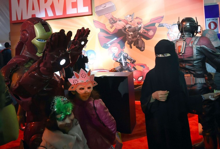 "A Saudi woman looks on as children pose for a photo with a man dressed up as ""Iron Man"" during the country's first ever Comic-Con event in the coastal city of Jeddah on February 16, 2017. The three-day festival of anime, pop art, video gaming and film-related events is part of a government initiative to bring more entertainment to Saudi Arabia which bans alcohol, public cinemas and theatre. (Fayez Nureldine/AFP/Getty Images)"