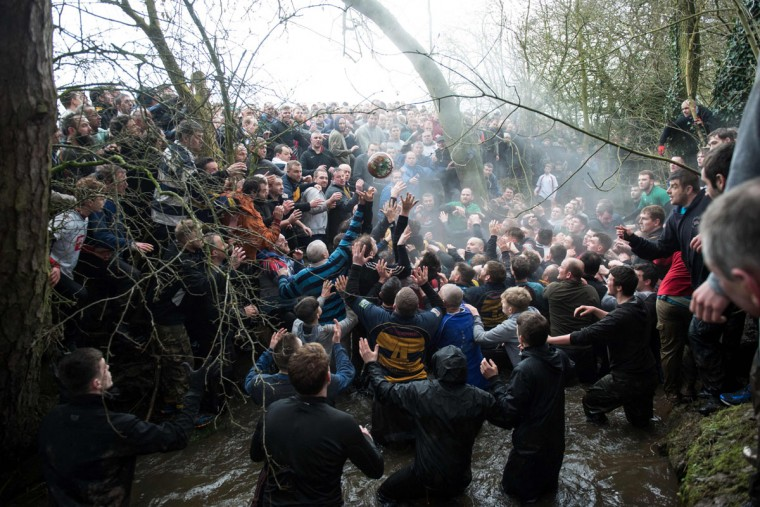 Competitors from the opposing teams, the Up'ards and the Down'ards, reach for the ball during the annual Royal Shrovetide Football Match in Ashbourne, northern England, on February 28, 2017. The mass-participation ball game involves two teams, whose players are defined by which side of a small brook that bisects the town they were born, aiming to score a goal, which are some three miles apart. The game, which has very few rules, is played over two 8 hour periods on Shrove Tuesday and Ash Wednesday. Royal Shrovetide Football is believed to have been played annually in Ashbourne since 1667. (AFP PHOTO / OLI SCARFF)