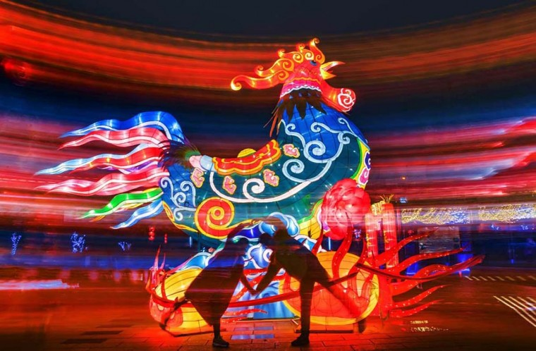 This photo taken on February 13, 2017 shows a Chinese couple posing for photographs with a rooster lantern display in Ningbo, east China's Zhejiang province. (AFP/Getty Images)