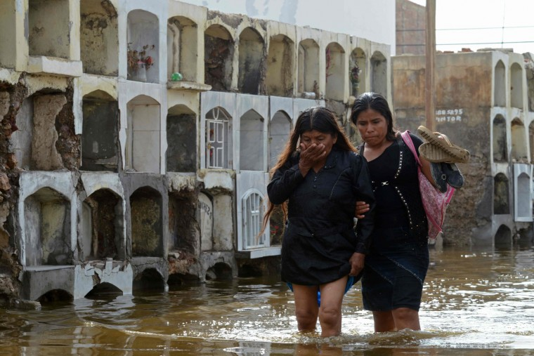 Women wade through stagnant water at the cemetery in Tucume, some 700 kilometers north of Lima, Peru, on February 6, 2017. Torrential rains, landslides and overflowing of rivers have killed 25 people and affected over 200,000 in Peru since the beginning of the year. (Cris Bouroncle/AFP/Getty Images)