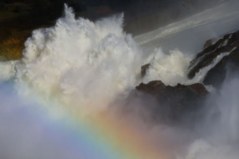 A rainbow is made by spray from water coming down the damaged main spillway of the Oroville Dam on Feb. 14, 2017, in Oroville, California. (Elijah Nouvelage/Getty Images)