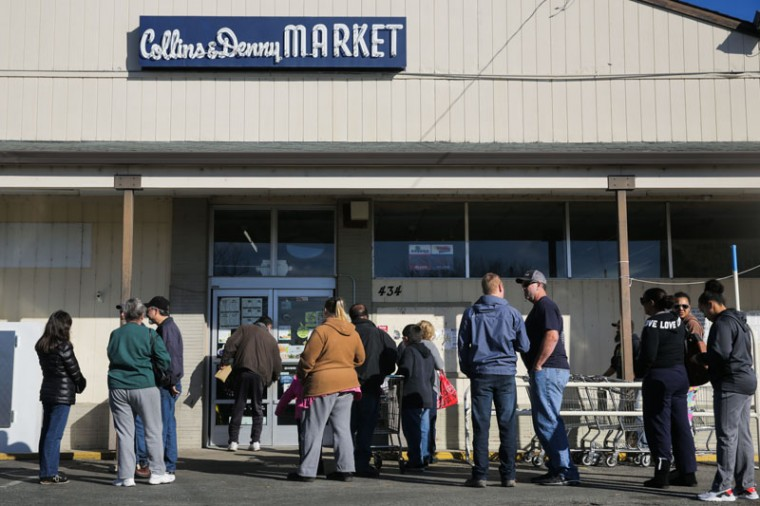 "People wait outside Collins and Denny Market as owner Mazen Hanoun opens the door on Feb. 14, 2017, in Oroville, California. People had converged on the parking lot after word spread on social media that the store might be opening. ""When people are here and refuse to leave I need to support those people,"" said Hanoun. Milk, food, diapers. My life is not better than them. They stay, I stay."" (Elijah Nouvelage/Getty Images)"