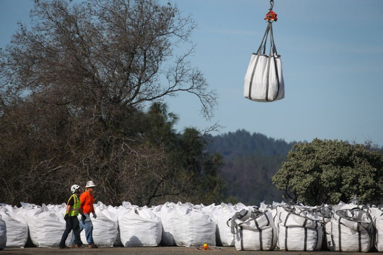 A helicopter picks up a bag of rocks at a staging area near the Oroville Dam on Feb. 14, 2017, in Oroville, California. More than 188,000 people were ordered to evacuate after a hole in the emergency spillway in the Oroville Dam threatened to flood the surrounding area.  (Elijah Nouvelage/Getty Images)