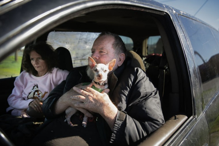 "Jack and Sheila Frazier of Oroville sit in a van with their dogs and their belongings in the parking lot of Collins and Denny Market on Feb. 14, 2017 in Oroville, California. ""If they tell us to leave again we'll leave,"" Jack said. ""[But] it's where we live."" (Elijah Nouvelage/Getty Images)"