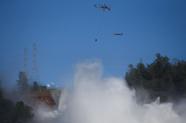 Helicopters carrying bags of rocks are seen above the damaged main spillway of the Oroville Dam on Feb. 14, 2017 in Oroville, California. (Elijah Nouvelage/Getty Images)
