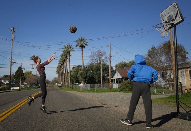 "Gabriella Watson, 14, plays basketball with Zack Wyman, 16, outside Wyman's home on Feb.14, 2017 in Oroville, California. ""When you grow up somewhere, even when you know something bad might happen, it's hard to leave it all behind,"" said Watson. More than 188,000 people were ordered to evacuate after a hole in the emergency spillway in the Oroville Dam threatened to flood the surrounding area. (Elijah Nouvelage/Getty Images)"