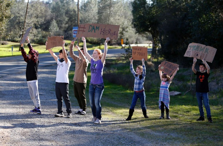 Young Oroville residents hold up signs for the workers who have been busy repairing the Oroville Dam in Oroville, California, on Feb. 14, 2017.  A sheriff lifted a mandatory evacuation order in northern California, which had impacted nearly 200,000 people in an area under threat of catastrophic failure at the tallest dam in the United States. (MONICA DAVEY/AFP/Getty Images)
