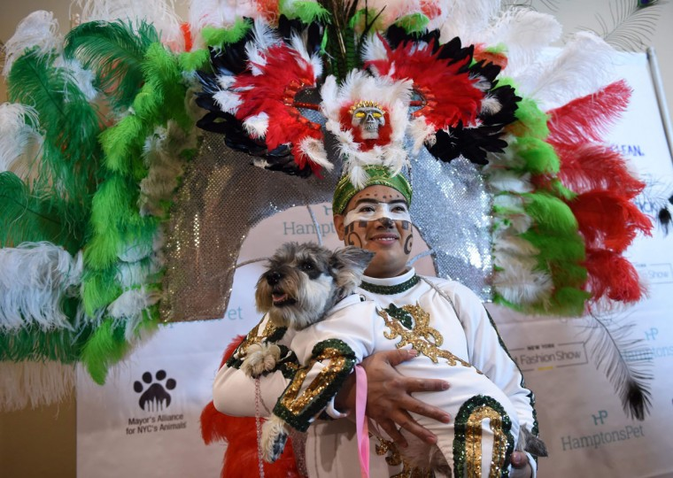 Miguel Garcia with his dog dressed in the fashion of Mexico and a contestant in the World Fashion Presents segment pose during the 14th Annual New York Pet Fashion Show presented by TropiClean at the Hotel Pennsylvania February 9, 2017. (TIMOTHY A. CLARY/AFP/Getty Images)