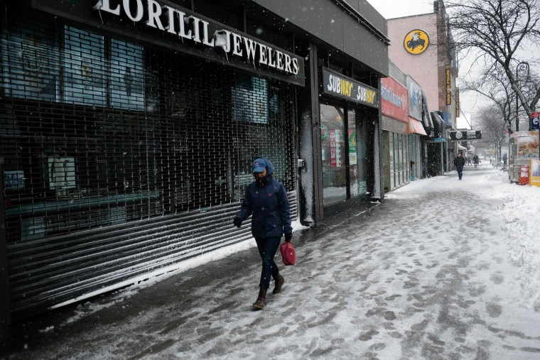 A woman walks past a closed store during a winter storm in New York on February 9, 2017. A heavy winter snow storm lashed the northeastern United States Thursday, subjecting New York to near blizzard-like conditions and forcing flight cancellations as schools and the United Nations closed. (Jewel Samad/AFP/Getty Images)