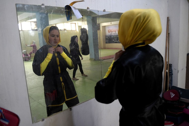 In this photograph taken on Janury 21, 2017, Afghan wushu martial arts trainer Sima Azimi, 20, is reflected in a mirror as she prepares for a training session in Kabul. Afghanistan's first female wushu trainer, Sima Azimi, 20, is training 20 Afghan girls aged between 14 - 20 at a wushu club in Kabul, after learning the sport while living as a refugee in Iran.