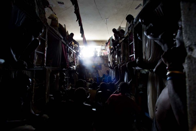 In this Feb. 13, 2017 photo, prisoners cram shoulder to shoulder to watch TV in their crowded cell inside the National Penitentiary in downtown Port-au-Prince, Haiti. Sentenced convicts and the far greater numbers of suspects still awaiting trial, pool together what little money they can scare up to buy small TVs and radios for their shared cells. (AP Photo/Dieu Nalio Chery)