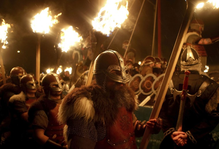 Members of the Jarl Squad dressed in Viking costumes carry flaming torches alongside their galley before torching it, during the Up Helly Aa Viking festival in Lerwick on the Shetland Isles, Scotland, Tuesday Jan. 31, 2017. (Jane Barlow/PA via AP)