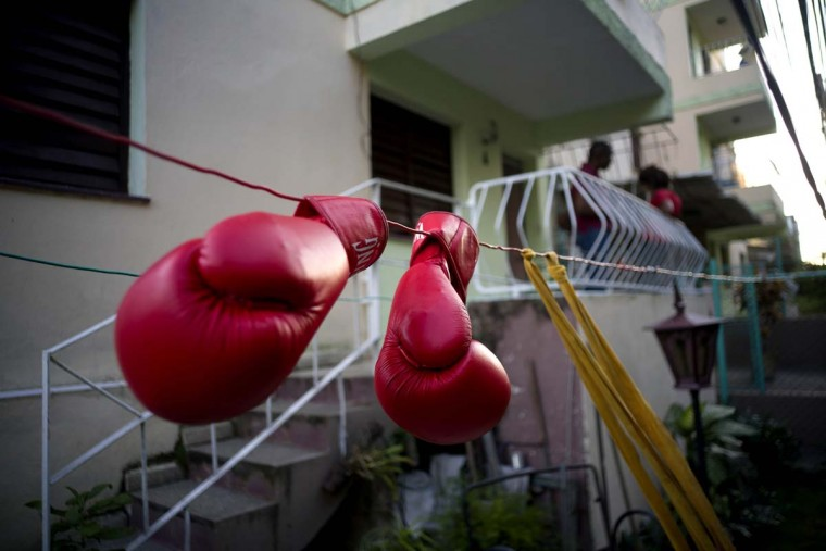 In this Jan. 19, 2017 photo, Idanerys Moreno's boxing gloves hang on a line to dry, after a training session in Havana, Cuba. Women were first allowed to box at the Olympics during the 2012 Summer Olympics but they are still not allowed to box in Cuba. (AP Photo/Ramon Espinosa)