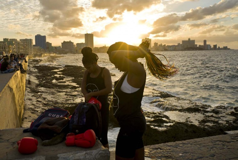 In this Jan. 30, 2017 photo, boxers Idamerys Moreno, left, and Legnis Cala, get ready for a photo session on Havana's Malecon, in Cuba. Moreno trains at least two hours a day after she gets off work, completing a routine that includes running several miles, lifting weights, hitting a punching bag and sparring with both women and men. (AP Photo/Ramon Espinosa)