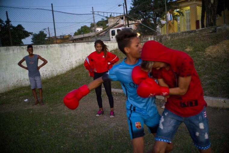 In this Jan. 19, 2017 photo, boxer Idamerys Moreno, center back, looks at children playing around, at a sports center in Havana, Cuba. Boxing has long been an athletic engine for Cuba, which has won 72 Olympic medals in that category but women are not allowed to box. (AP Photo/Ramon Espinosa)
