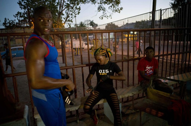 "In this Jan. 24, 2017 photo, Olympic silver medalist Emilio Correa Jr., left, mentors female boxer Legnis Cala, center, at a sports center in Havana, Cuba. ""They can bring more glory to the Cuban sport,"" Correa said. ""They are diamonds in the rough. The motor skills, the explosive nature and the energy of Cuban boxers are also present in these women."" (AP Photo/Ramon Espinosa)"