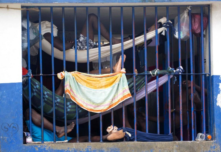 In this Feb. 13, 2017 photo, prisoners rest in makeshift hammocks inside the National Penitentiary in downtown Port-au-Prince, Haiti. Prisoners in Haiti's largest prison are crammed shoulder-to-shoulder in cellblocks so overcrowded they have to sleep in makeshift hammocks suspended from the ceiling or squeeze four to a bunk. (AP Photo/Dieu Nalio Chery)