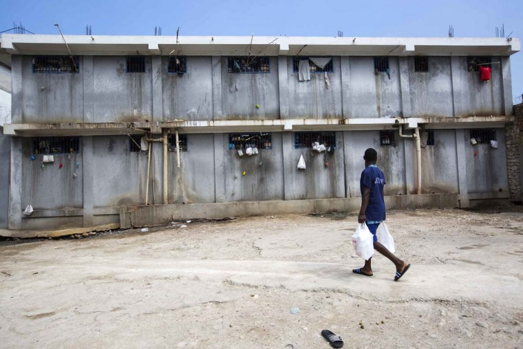 In this Feb. 13, 2017 photo, a prisoner hauling food that brought him, walks past a prison building at the National Penitentiary in downtown Port-au-Prince, Haiti. Prison authorities say they try their best to meet inmates' needs, but repeatedly receive insufficient funds from the state to buy food and cooking fuel. Some inmates are provided meals by visiting relatives and others are permitted by guards to meet with contacts to bring in food, cigarettes and other things. (AP Photo/Dieu Nalio Chery)