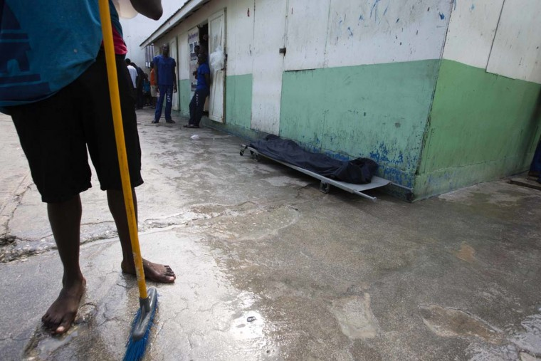 In this Feb. 13, 2017 photo, a prisoner stands near the body of an inmate, covered with a plastic tarp, who died of malnutrition inside the National Penitentiary in downtown Port-au-Prince, Haiti. Overcrowding, malnutrition and infectious diseases that flourish in jammed quarters has led to an upsurge of inmate deaths. (AP Photo/Dieu Nalio Chery)