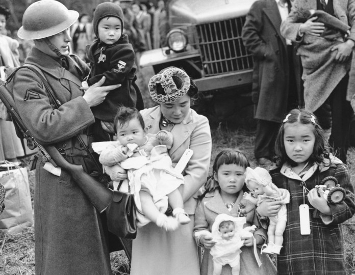 In this March 30, 1942 file photo, Cpl. George Bushy, left, a member of the military guard which supervised the departure of 237 Japanese people for California, holds the youngest child of Shigeho Kitamoto, center, as she and her children are evacuated from Bainbridge Island, Wash. Roughly 120,000 Japanese immigrants and Japanese-Americans were sent to desolate camps that dotted the West because the government claimed they might plot against the U.S. (AP Photo/File)