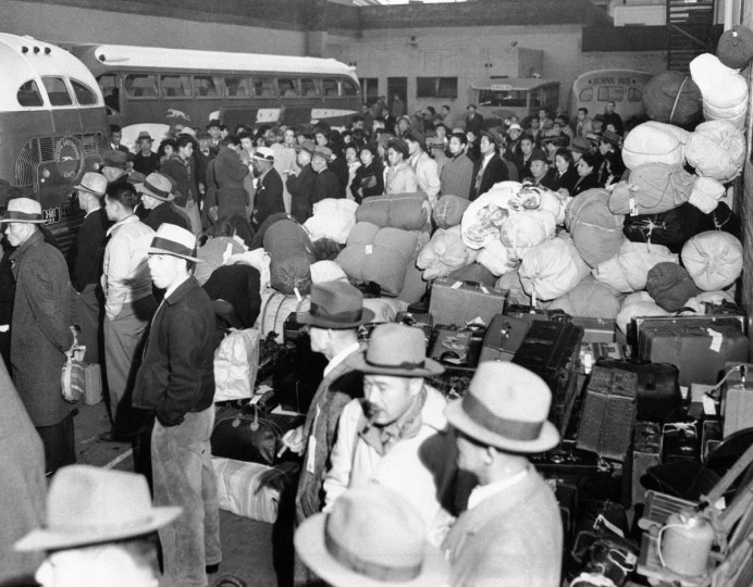 In this March 21, 1942 file photo, people of Japanese ancestry board buses in Los Angeles, for Owens Valley, 235 miles north, where the government's first alien reception center is under construction. The nearly 100 people were skilled workers who will help prepare the camp for thousands of others to arrive later. Roughly 120,000 Japanese immigrants and Japanese-Americans were sent to desolate camps that dotted the West because the government claimed they might plot against the U.S. (AP Photo/File)