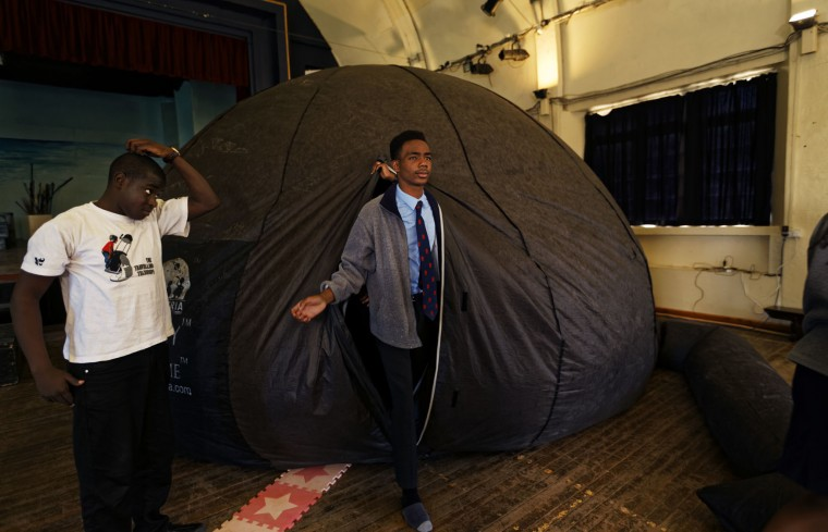In this photo taken Friday, Feb. 3, 2017, a student walks out of an inflatable planetarium, during a visit by The Traveling Telescope to show students the science of astronomy, at St Andrew's School near Molo in Kenya's Rift Valley. Although Kenya lies on the equator and has dramatic nighttime skies in rural areas, children find it hard to name planets and other bodies as astronomy is rarely taught in schools - but that is changing as The Traveling Telescope visits some of the country's most remote areas with telescopes and virtual reality goggles. (AP Photo/Ben Curtis)