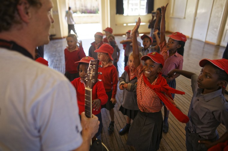 In this photo taken Friday, Feb. 3, 2017, students raise their hands to astronomer and company co-founder Daniel Chu Owen, left, during a visit by The Traveling Telescope to show students the science of astronomy, at St Andrew's School near Molo in Kenya's Rift Valley. Although Kenya lies on the equator and has dramatic nighttime skies in rural areas, children find it hard to name planets and other bodies as astronomy is rarely taught in schools - but that is changing as The Traveling Telescope visits some of the country's most remote areas with telescopes and virtual reality goggles. (AP Photo/Ben Curtis)
