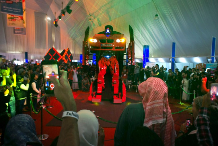 "Visitors watch the Turkish made robot ""Letrons"", as it morphs from a car to a giant robot during the Saudi Comic Con (SCC) which is the first event of its kind to be held in Jiddah, Saudi Arabia, Friday, Feb. 17, 2017. (AP Photo)"