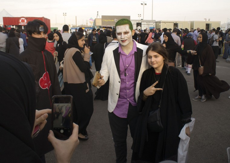 A visitor poses for a picture with a man disguised as The Joker, during the Saudi Comic Con (SCC) which is the first event of its kind to be held in Jiddah, Saudi Arabia, Friday, Feb. 17, 2017. (AP Photo)