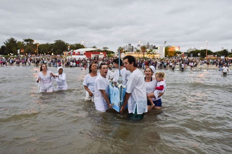 Worshippers enter ocean waters singing and leading a boat with offerings for the African sea goddess Yemanja, in Montevideo, Uruguay, Thursday, Feb. 2, 2017. Thousands of worshippers come to the beach on Yemanja's feast day, bearing candles, flowers, perfumes and fruit to show their gratitude for her blessings. The celebration coincides with the Roman Catholic feast day of the Virgin of Candelaria, marked Feb. 2. (AP Photo/Matilde Campodonico)