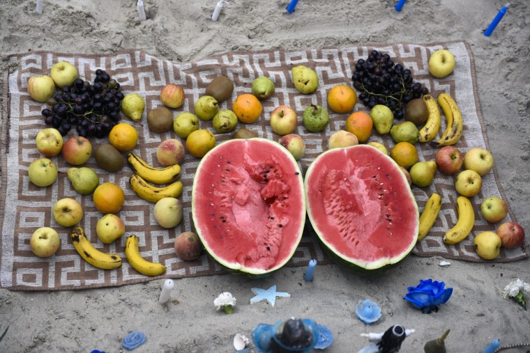Offerings for the African sea goddess Yemanja are arranged on a towel at a beach in Montevideo, Uruguay, Thursday, Feb. 2, 2017. Thousands of worshippers come to the beach on Yemanja's feast day, bearing candles, flowers, perfumes and fruit to show their gratitude for her blessings. The celebration coincides with the Roman Catholic feast day of the Virgin of Candelaria, marked Feb. 2. (AP Photo/Matilde Campodonico)