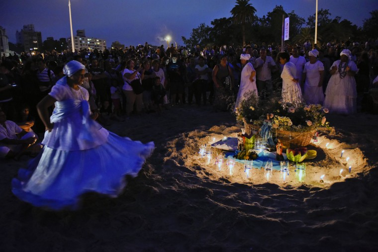 A woman dances around an offering for the African sea goddess Yemanja, in Montevideo, Uruguay, Thursday, Feb. 2, 2017. Thousands of worshippers come to the beach on Yemanja's feast day, bearing candles, flowers, perfumes and fruit to show their gratitude for her blessings. The celebration coincides with the Roman Catholic feast day of the Virgin of Candelaria, marked Feb. 2. (AP Photo/Matilde Campodonico)