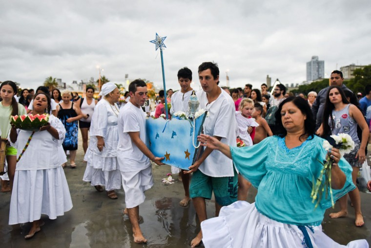 Worshippers carry a boat filled with offerings for the African sea goddess Yemanja, at a beach in Montevideo, Uruguay, Thursday, Feb. 2, 2017. Thousands of worshippers come to the beach on Yemanja's feast day, bearing candles, flowers, perfumes and fruit to show their gratitude for her blessings. The celebration coincides with the Roman Catholic feast day of the Virgin of Candelaria, marked Feb. 2. (AP Photo/Matilde Campodonico)