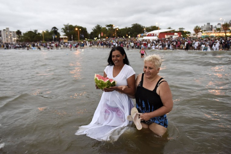 Two women enter the sea with an offering for the African sea goddess Yemanja, during a ceremony honoring the deity in Montevideo, Uruguay, Thursday, Feb. 2, 2017. Thousands of worshippers come to the beach on Yemanja's feast day, bearing candles, flowers, perfumes and and fruit to show their gratitude for her blessings. The celebration coincides with the Roman Catholic feast day of the Virgin of Candelaria, marked Feb. 2. (AP Photo/Matilde Campodonico)