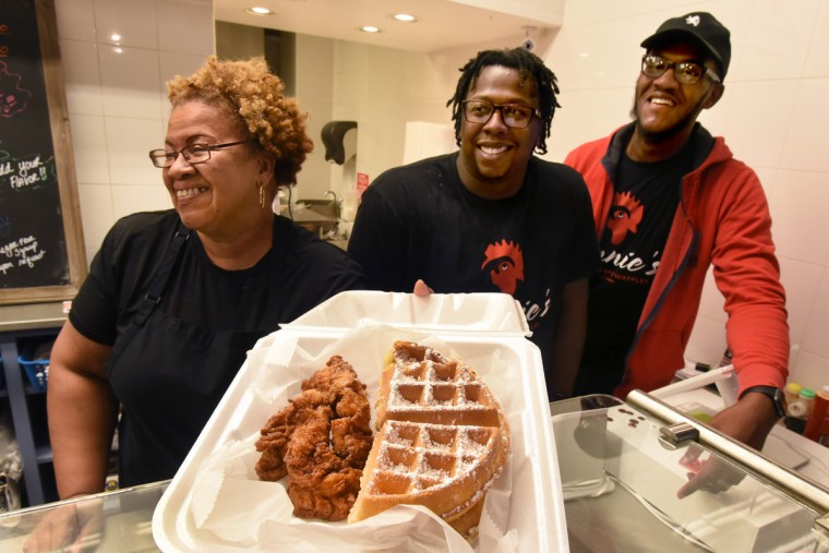 Connie Parker, left, presents a popular item, the buttermilk waffle with chicken tenders, to a customer. Her sons Khari Parker, center, and Shawn Parker, right, operate Connie's Chicken & Waffles, but she helps out. The brothers opened their stall last June in the Arcade near the Eutaw Street entrance. (Amy Davis/Baltimore Sun)
