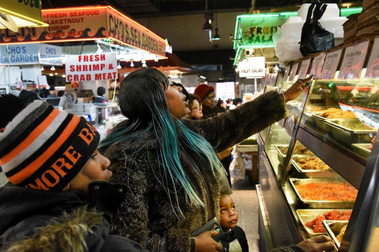April Washington of East Baltimore, with her son, Tommy Graham, 14, left, and a nephew, Kyrell Cooke, 3, behind her, at one of her favorite vendors, Park's Fried Chicken. She comes here about three times a week. (Amy Davis/Baltimore Sun)