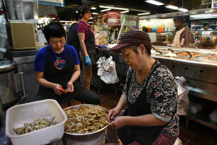 Ping Chen, left, and Chi Tsang, right, shell shrimp at the Blue Island Malaysian stall, owned by Sabrina Chen. (Amy Davis/Baltimore Sun)