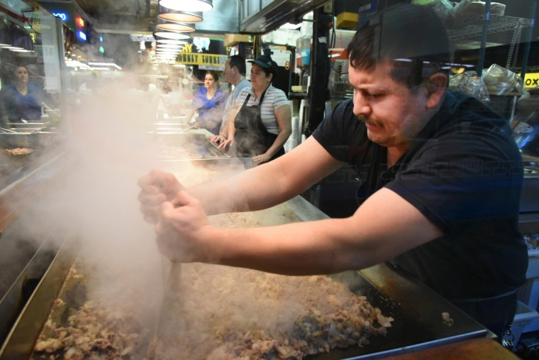 Luis Esquivel chops up beef on the grill for cheese steak subs at Andy's Barbecue in Lexington Market east building. (Amy Davis/Baltimore Sun)