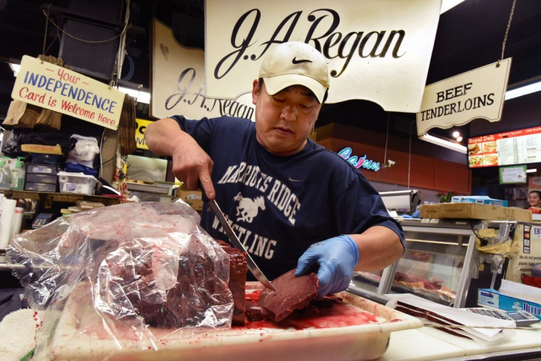 Philip Cho, at J.A. Regan, slices baby beef liver for a customer. J.A. Regan, one of three butchers at Lexington Market, was purchased by Philip Cho and his wife Grace two years ago. Philip Cho says their best sellers are slab bacon, ground round, and baby beef liver. Their customers like getting custom cuts rather than pre-packaged meat. (Amy Davis/Baltimore Sun)