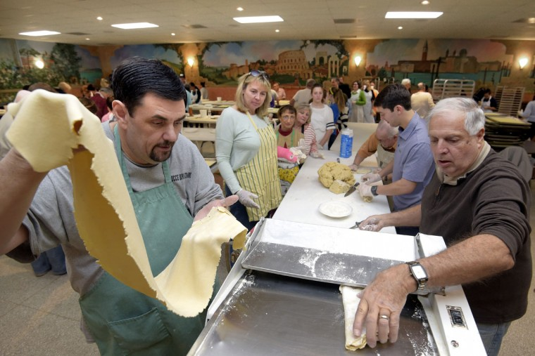 Tony Walmsley, left, and Armand Esposito, right, feed ravioli dough through the rolling machine as volunteers wait to carry off the long dough strips to their work stations. (Algerina Perna/Baltimore Sun)