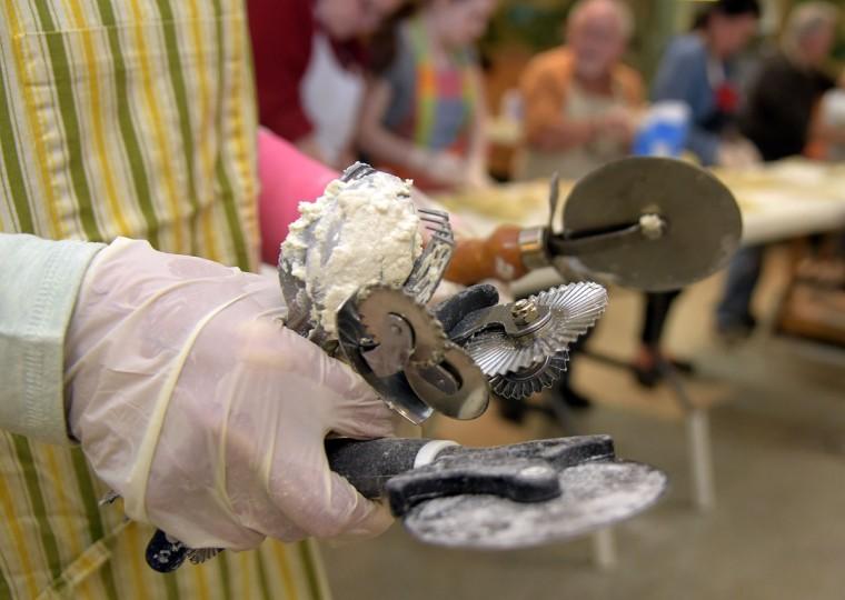 A volunteer gathers the utensils used in making ravioli. (Algerina Perna/Baltimore Sun)