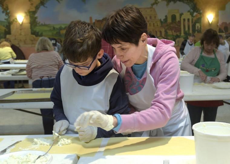 Laura Barrett-Nutting helps her son Joshua Barrett put filling onto the ravioli dough. (Algerina Perna/Baltimore Sun)