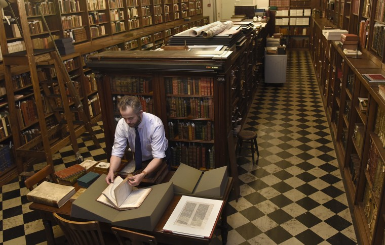 Paul Espinosa, curator of the Peabody Library, looks at rare books in the library's Rare Books Room.  (Barbara Haddock Taylor/Baltimore Sun)